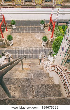 High stairs leading to the stupa in Temple of Dawn, Wat Arun, Bangkok, Thailand. Wat Arun is among the best known of Thai landmarks