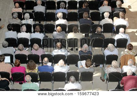 Group of unknown business people sitting and listening on scientical presentation