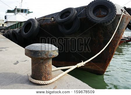 Old Dock Cleat Tied-up by a rusty steel ship