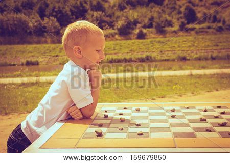 Draughts board game. Little boy clever child kid playing checkers thinking outdoor in the park side view. Childhood and development