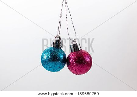 Christmas balls hanging in midair against a white background