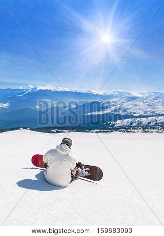 Snowboarder relaxing in high snowy mountains against sun sunshine rays active winter sports holidays travel at ski health resort concept
