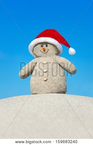 Positive creative sandy snowman in red Santa hat at beach. New Year and Christmas holiday travel destinations in hot countries concept
