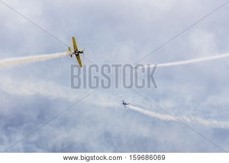 avia show. 3 small aircrafts depict acrobatics in the sky blowing smoke