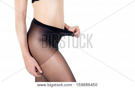 Woman tends black elastic tights on white background