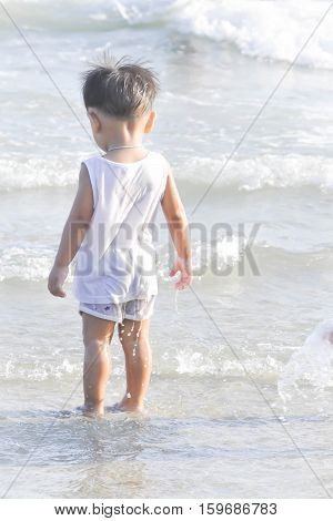 a boy is standing on the beach