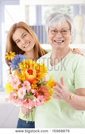Happy senior mother and daughter smiling at mother's day, holding flowers.?
