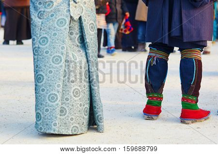 Couple in traditional Tibetan costumes focus is on the man's legs