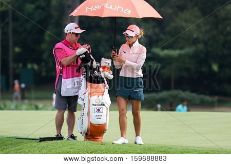KUALA LUMPUR, MALAYSIA - OCTOBER 29, 2016: Jenny Shin of South Korea checks with her caddie on the fairway of the TPC Golf Course at the 2016 Sime Darby LPGA Malaysia golf tournament.
