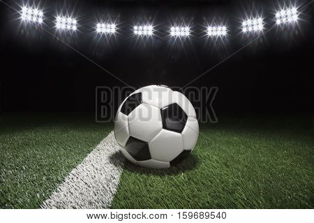 Traditional soccer ball on grass field with stripe under lights at night