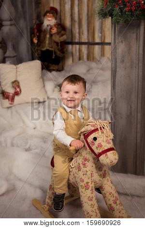 Little boy in Christmas dress playing with toy horse. Christmas and new year concept.