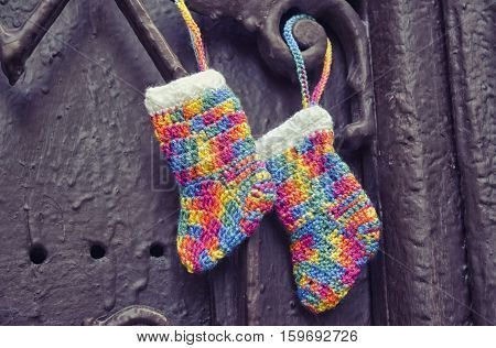 Handmade knitting socks with ornament hanging on ribbon. Christmas handmade decorations. Christmas colored boots in anticipation of Santa's gifts. Colorful Christmas stocking decoration element.