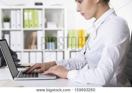 Side view of a concentrated office employee wearing a white blouse and typing at her laptop in an office with folders of different colors