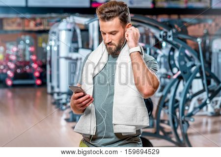 Lifestyle portrait of handsome muscular man listening to the music with mobile phone after the training in the sport gym