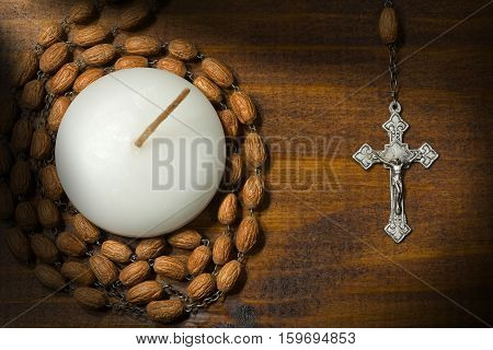 Old silver crucifix and rosary with wooden beads and a white votive candle (tea light). On a wooden background