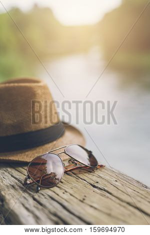 Hat and glasses with lake view Travel concept