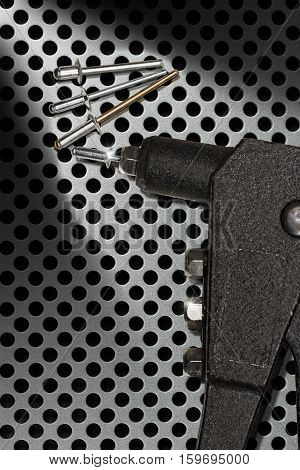 Detail of a black rivet gun (hand riveter) with rivets on a metal background with holes
