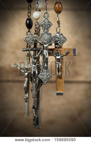 Detail of a group of silver crucifixes with rosary beads. Hanging on a wooden background with dark shadows