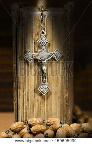 Silver crucifix and rosary with wooden beads on a old Holy Bible with dark shadows