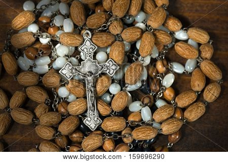 Detail an old silver crucifix with many rosary beads on a wooden background