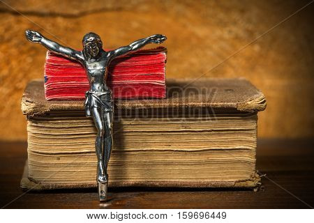 Silver crucifix without the cross and two Holy Bibles on a wooden table with dark shadows