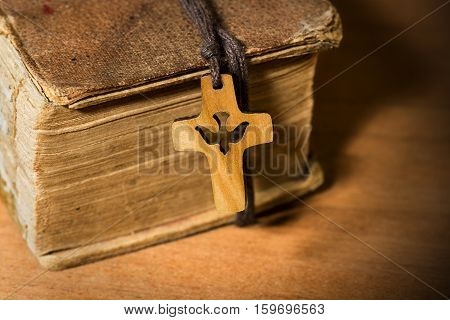 Small wooden crucifix with a dove and rope on an old Holy Bible