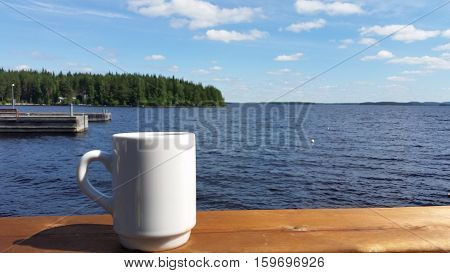 White Coffee Cup on Banister with Summer Seascape