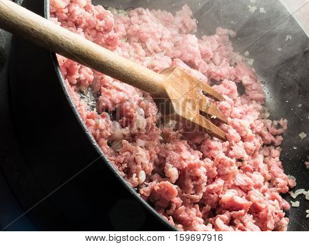 Some smoking ground beef in a frying pan mixed with onions