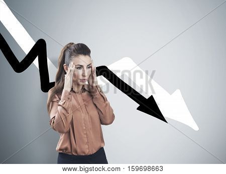 Stressed Woman And Declining Graphs On Gray Wall