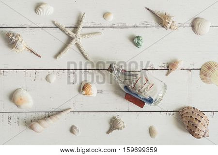 sail boat toy model and shell on white wooden background Travel concept