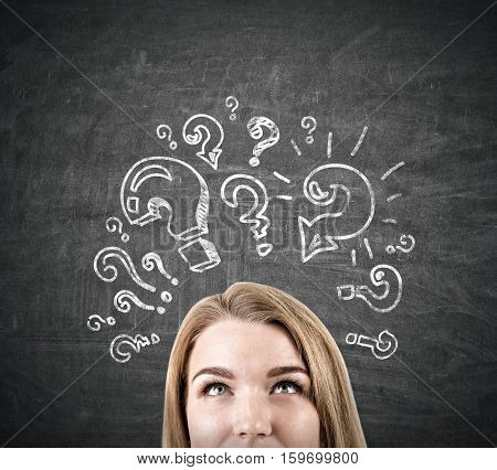 Close up of a blond woman's head near a blackboard with a question mark sketches on it. Concept of too many questions