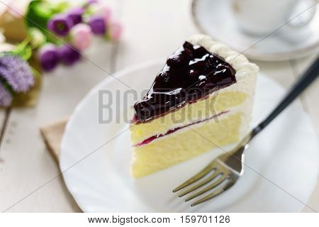 blueberry cake and cup of tea on white wooden table