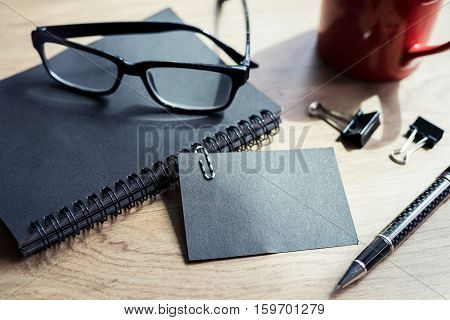 Cup of coffee with black notebook on wooden desk with copy space