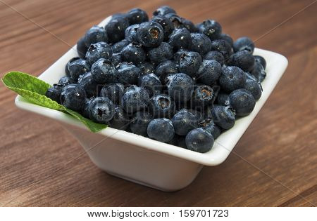 fresh bilberries or blueberries in small bowls on a rustic table selective focus