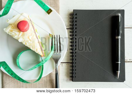 Fancy cake with measure tape and notebook on white wooden background healthy concept