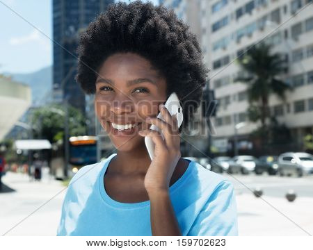 Happy african american girl with cell phone outdoor in the city in the summer