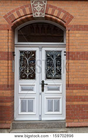 Gray double Door with windows in a red brick house