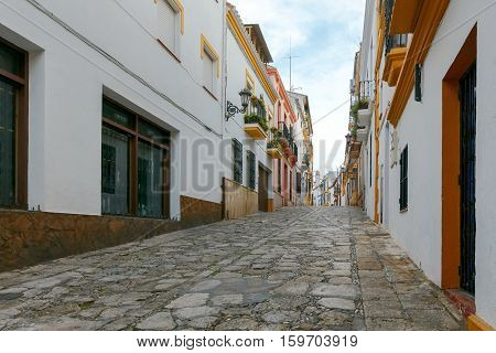 The narrow traditional street in the city of Ronda. Andalusia. Spain.