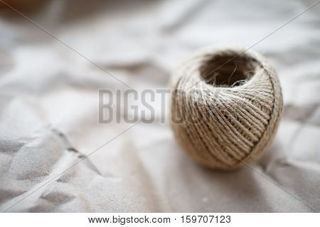 A ball of twine on a crumpled kraft paper