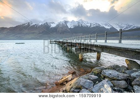 Wooden jetty with mountain at Glenorchy lake New Zealand.