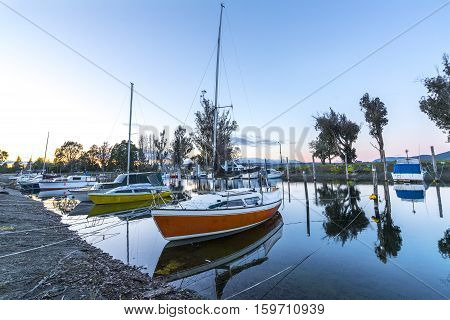 A row of boats with reflection during sunrise moment.