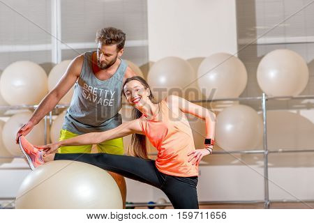 Young woman making exercise with fitball with personal trainer in the fitness room