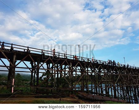 KANCHANABURI THAILAND - NOVEMBER 25: unidentified tourist enjoying and walking on the old wooden Mon Bridge in Sangkhla Buri on November 25 2016 in Kanchanaburi Thailand