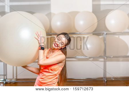 Portrait of the young smiling woman with fitball in the fitness gym