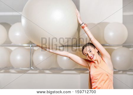Young woman making exercise with fitball in the fitness gym