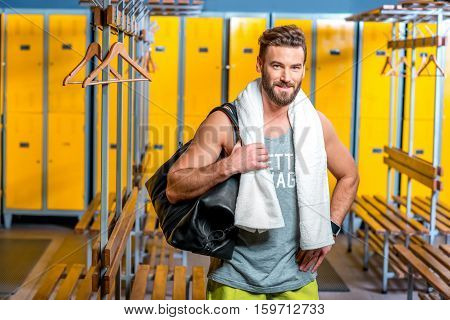 Sports man standing with towel and bag in the locker room at the gym