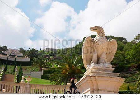 HAIFA ISRAEL - CIRCA SEP 2016: View of the Bahai Gardens stone statue of an eagle in the foreground