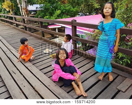 KANCHANABURI THAILAND - NOVEMBER 25: unidentified Burmese girls preparing thanaka powder for traveler at the old wooden Mon Bridge in Sangkhla Buri on November 25 2016 in Kanchanaburi Thailand