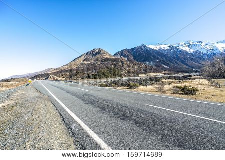 Straight empty highway leading into Aoraki Mount Cook New Zealand