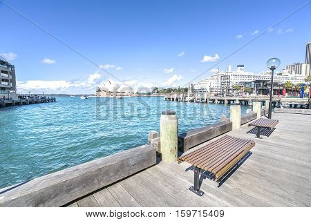 SYDNEY AUSTRALIA - AUGUST 26 2016: Wooden brench in front of Opera House in Sydney harbour. Ferries are used by commuters as a pleasant way to get into the city.